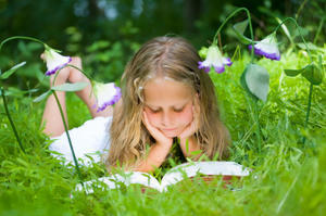 Girl reading outside in the grass