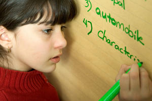 Girl writing spelling words on the flip chart